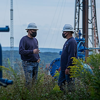 two workers wearing masks at rig site