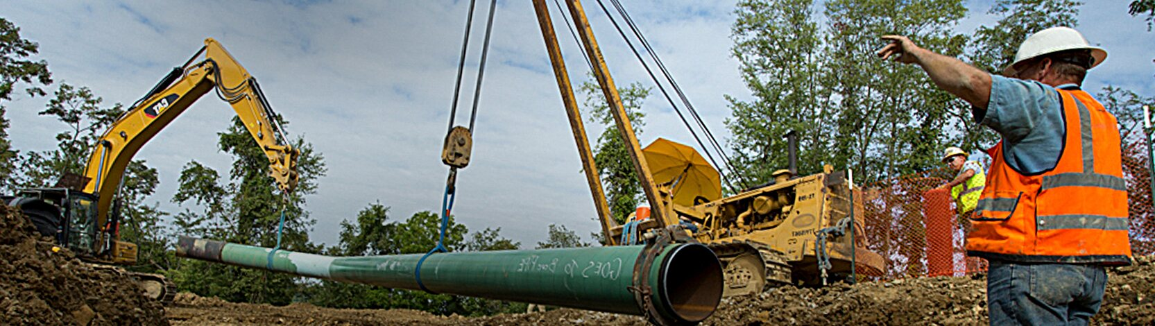 worker directing the laying of pipeline