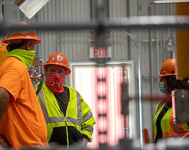 masked workers conversing